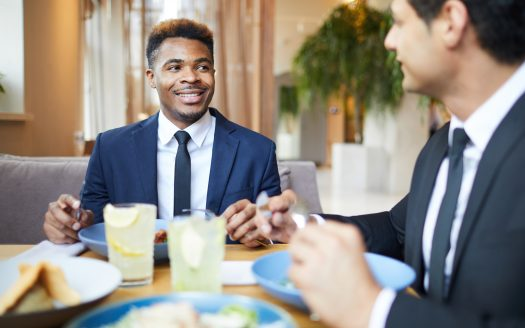 Smiling African businessman has a business lunch together with his colleague, they talking and eating at restaurant